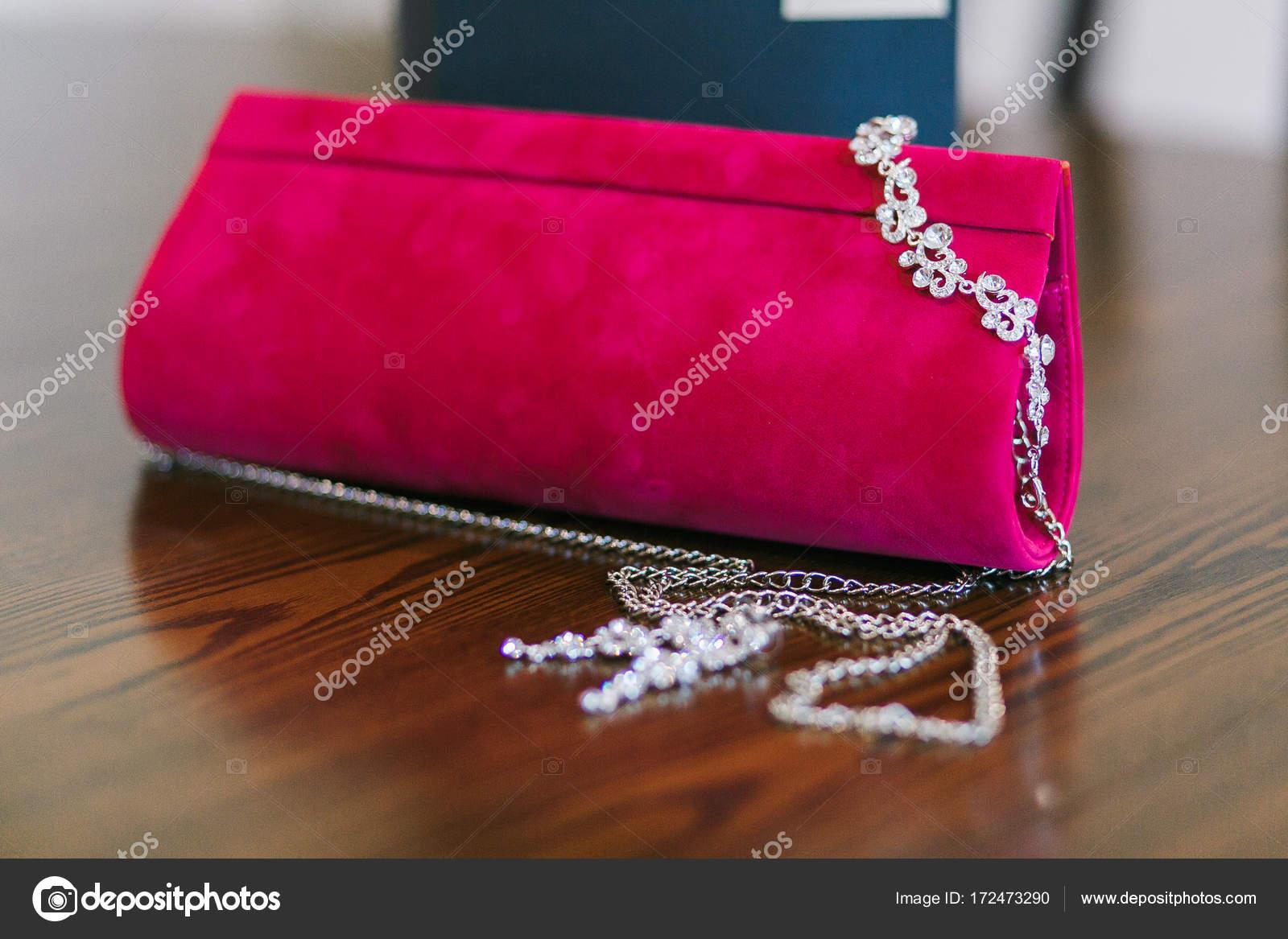 Houten Tafel Behandelen : Kleine rode fluwelen portemonnee met metalen ketting op houten