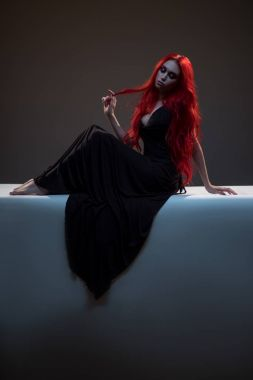 red haired woman in black dress