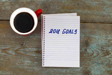 2018 goals list with notebook, cup of coffee on wooden desk. To