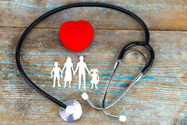 Paper silhouette of family, stethoscope and heart on wooden back