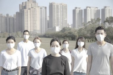 young group wearing mouth mask against air pollution in city
