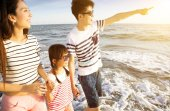 happy family walking on the beach at summer vacation