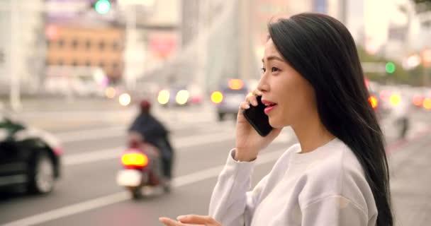 mladá žena hledá chytrý telefon ve městě v noci
