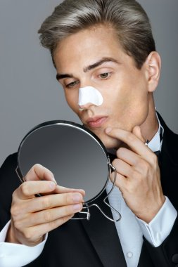 Man, looking in the mirror, pointing at his acne