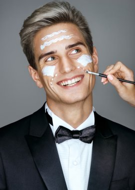 Happy imposing man with cream lines on face, spa treatment