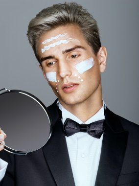 Fashion man with cosmetic cream treatment on his face, looking in the mirror.