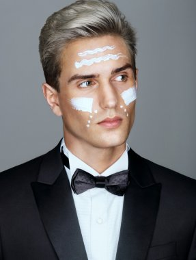 Beautiful face of imposing man with cosmetic cream on cheeks