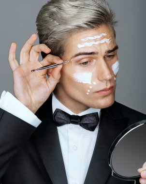 Intelligent and handsome man tweezing the hair on his face