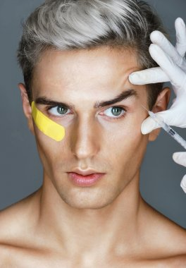 Glamorous man gets beauty injection in eye area from doctor.