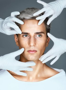 Hands of doctors in medical gloves touching face of beautiful young man.