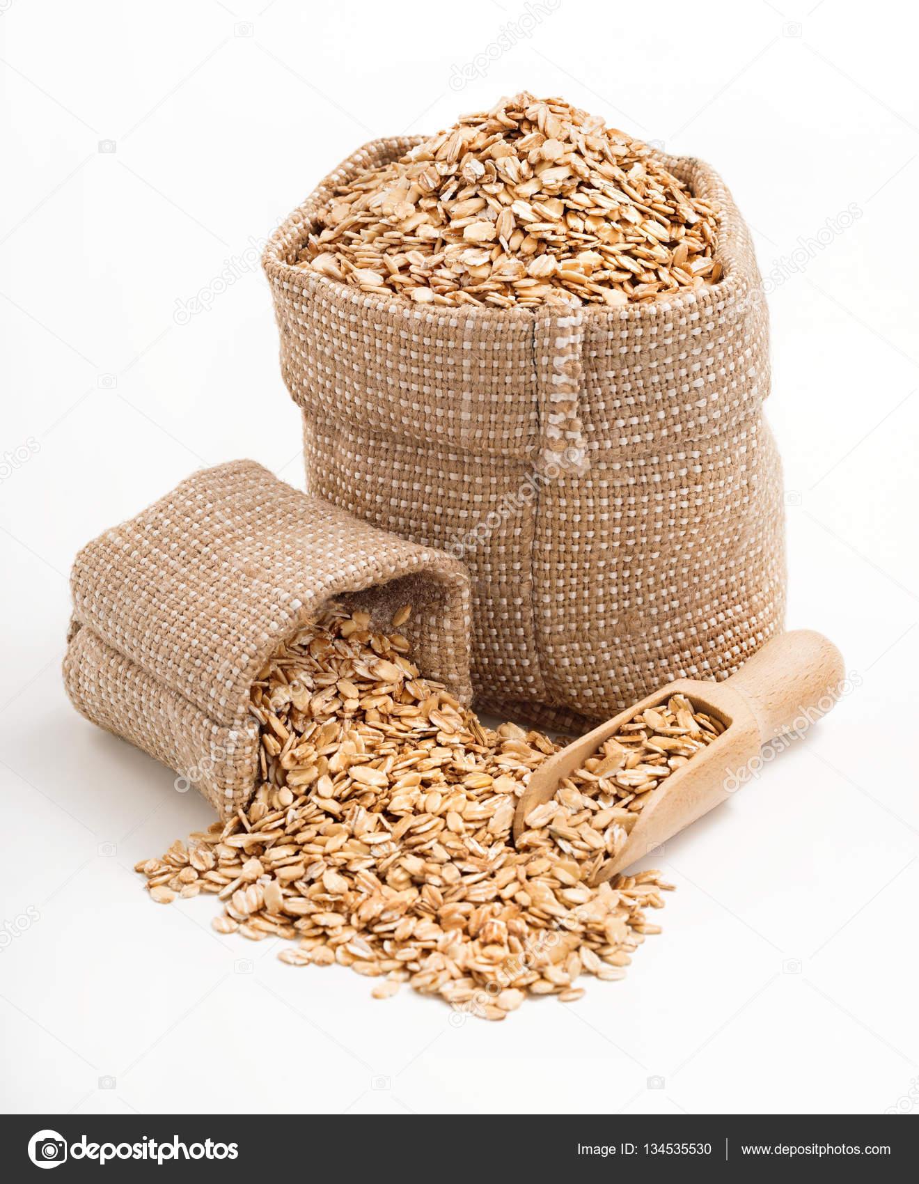 harina de avena en bolsa de arpillera con cucharada de madera aislada sobre fondo blanco u