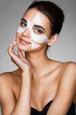Okouzlující mladá žena s bavlnou obličejové masky
