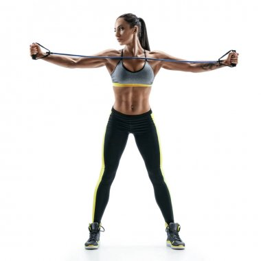 Beautiful strong model performs exercises for the muscles of the chest using an  resistance bands.