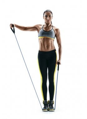 Attractive strong girl performs exercises using an resistance bands and looking at the camera.