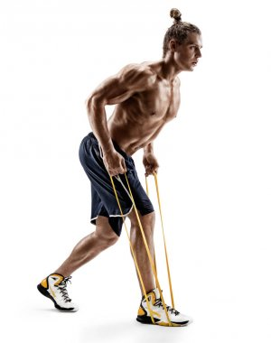 Sporty man performs exercises using a resistance band.