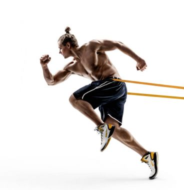 Sporty man runner in silhouette using a resistance band in his exercise routine