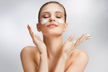 Beautiful woman applying moisturizing cream on her face. Photo of woman with flawless skin on grey background. Skin care and beauty concept