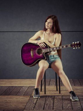 Redhead woman playing acoustic guitar