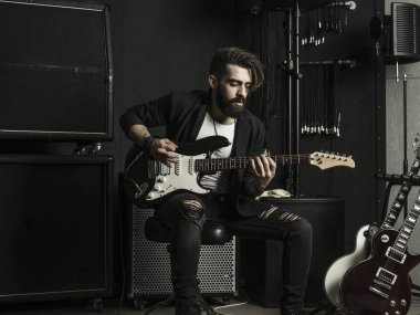 Man playing his electric guitar in a music studio