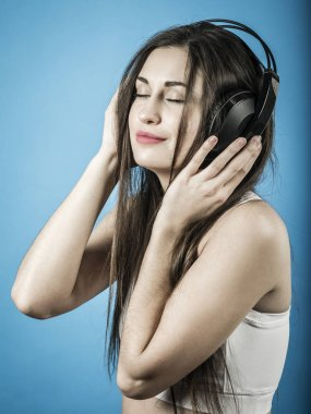 Beautiful woman listening to music with headphones