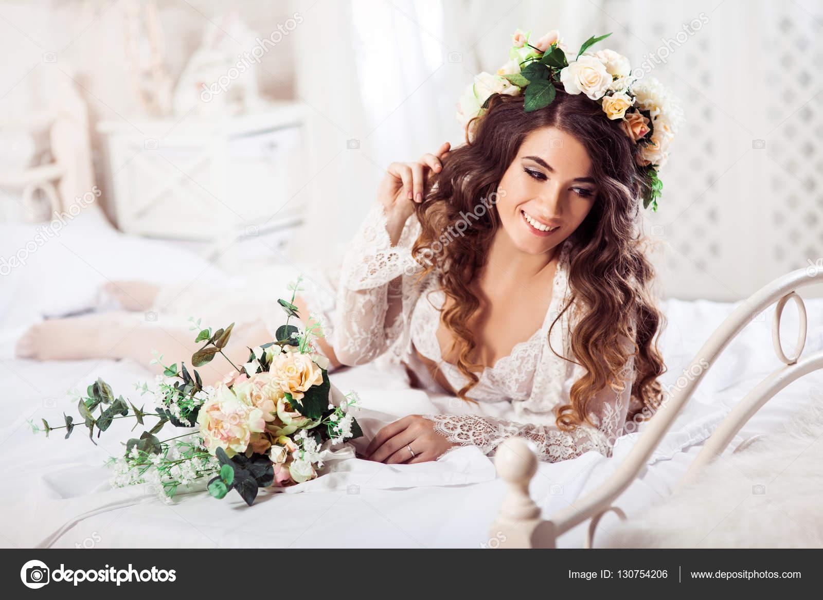 Sexy Braut Strauß am Morgen auf einem Bett liegend gekleidet in ...