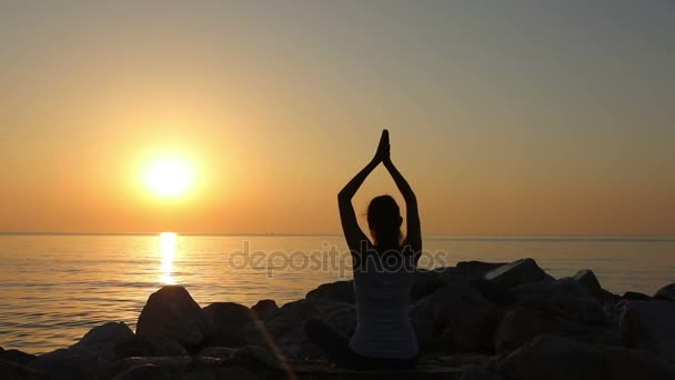 Morning meditation, woman practices yoga on the seashore