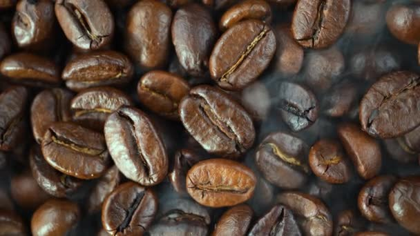 Roasted coffee beans are mixed with a spoon with smoke in a pan.