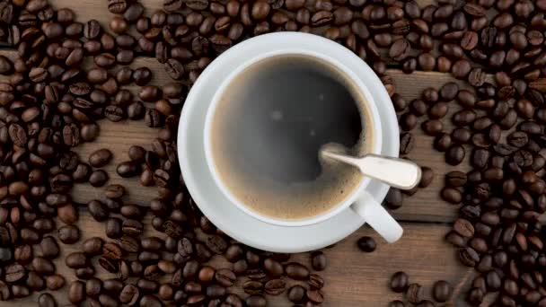 Horká káva v šálku s párou na starém pozadí.