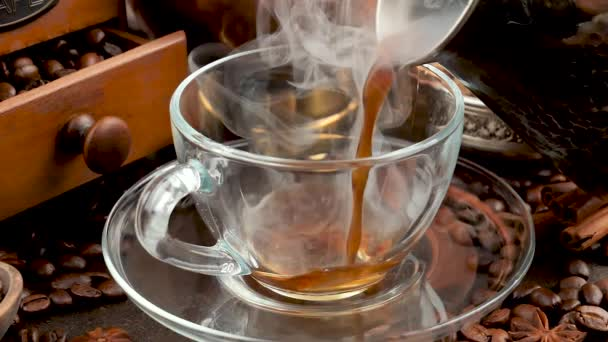 Coffee with steam poured from a coffee pot into a cup
