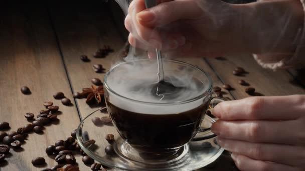 Míchání vařící kávy v šálku s lžičkou