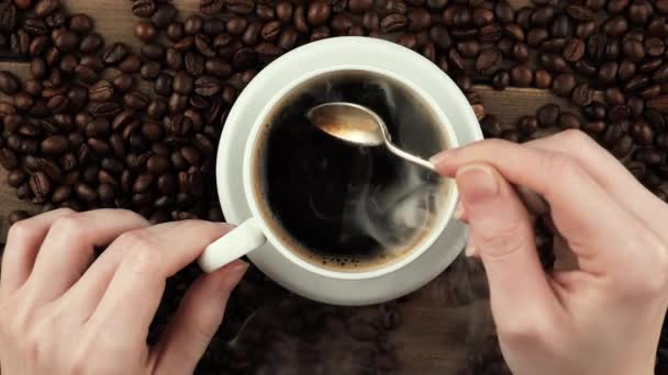 Mixing steaming coffee in a cup with a spoon