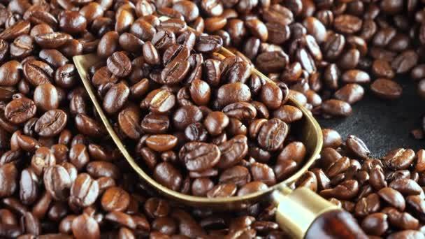 A pörkölt kávébabot egy kanállal keverik, füsttel a serpenyőben..