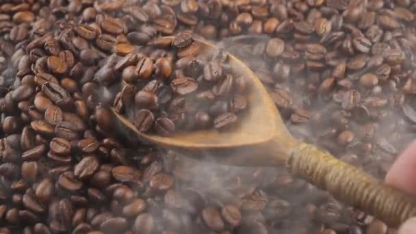 Pražená kávová zrna se smíchají se lžící s kouřem v pánvi.
