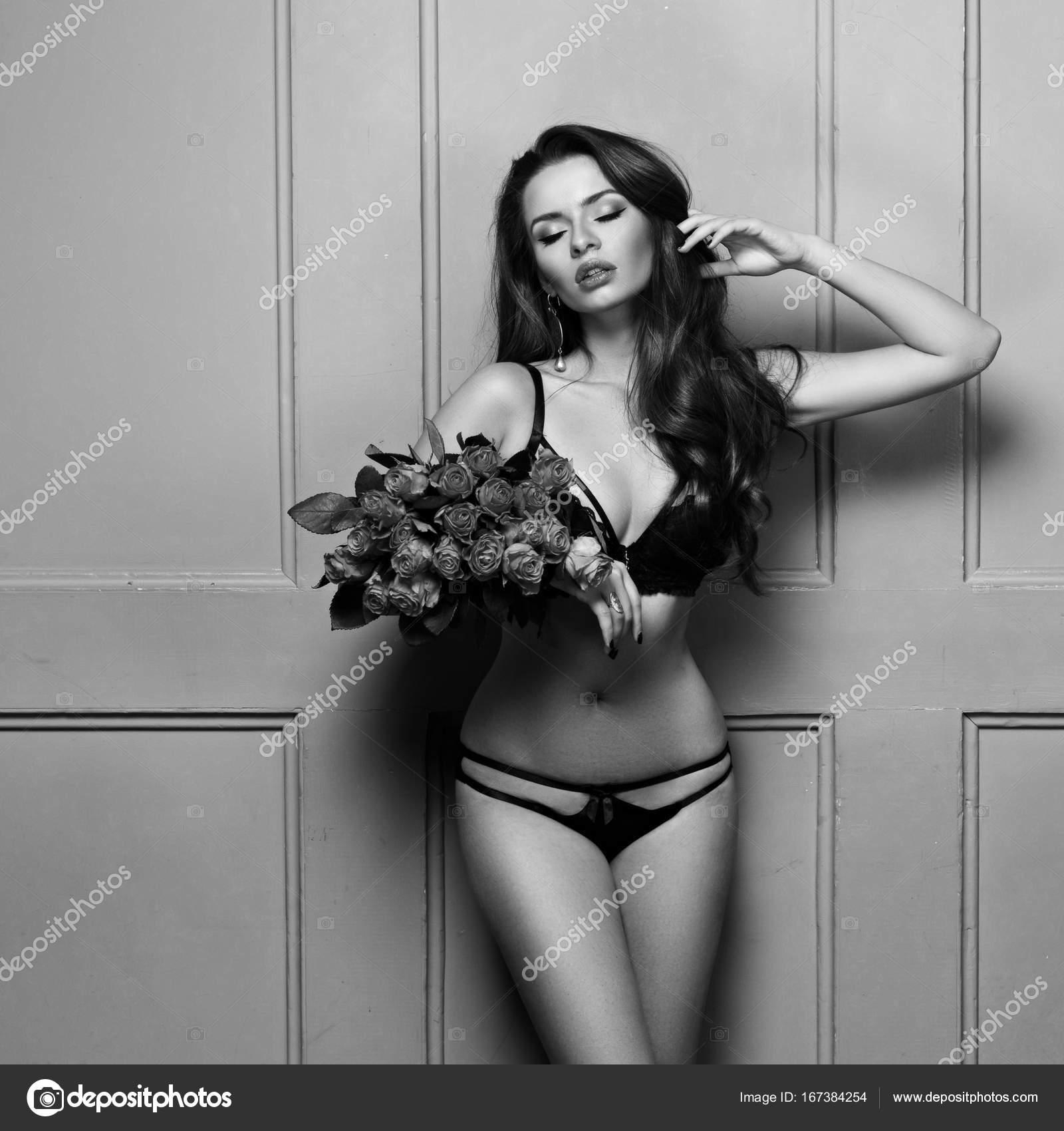8f409c951 Mulher morena sedutora em lingerie preta com buquê de rosas — Fotografia de  Stock