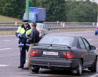The inspector of traffic police check the documents of the driver on the track