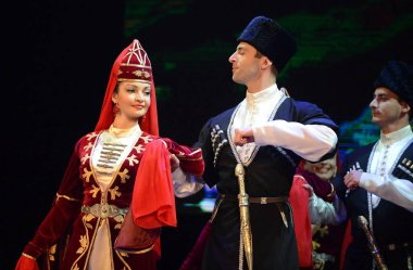 Ossetians in traditional dress dancing folk mountain dance.