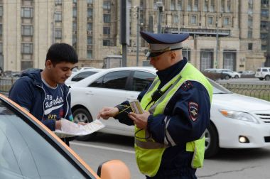 The inspector dorozhno-patrol service of the police checks the documents of a taxi driver in Central Moscow.