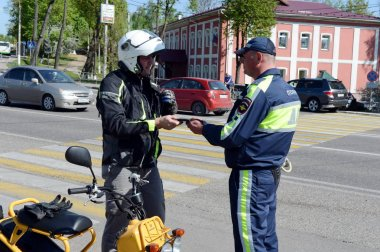 The inspector of traffic police checks the documents of the motorcycle.