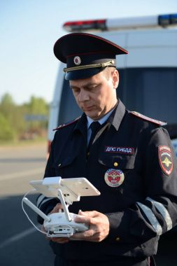The inspector of traffic police services monitors the route using the quadcopter.