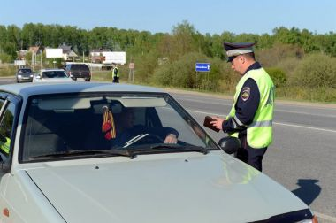 The officer of the police checks documents of the driver of the car.