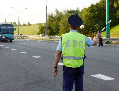 The inspector of the road police patrol stops the intercity bus for checking.