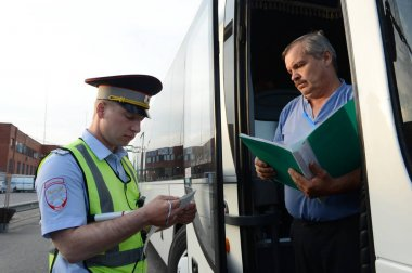 The inspector of the road police patrol checks documents from the driver of the intercity passenger bus.