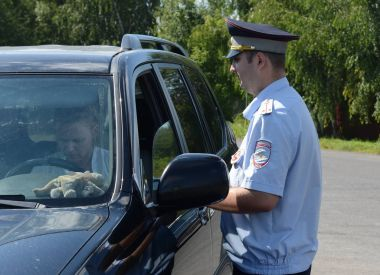 The inspector of the road police patrol checks the documents of the driver of the car.