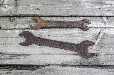 Two spanners on an old wooden table