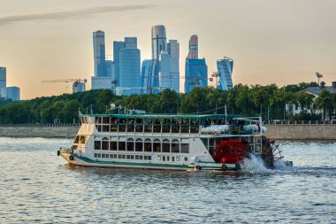 Moscow, Russia - June 15, 2019: Pleasure tourist boat on the Moscow river in the evening. In the background are the skyscrapers of the business center.