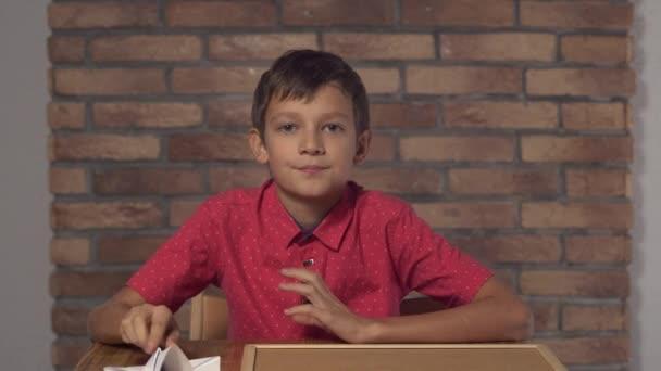 dítě sedí u stolu, držel flipchart s nápisy mouchou na zdi červených cihel pozadí