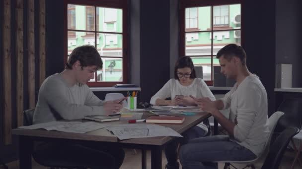 Mladí zaměstnanci s klientem používají zařízení na setkání