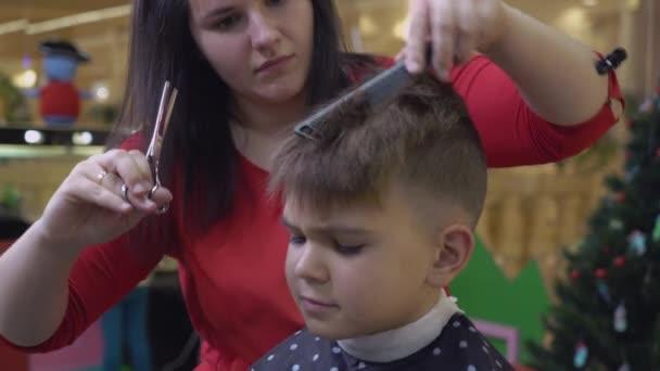 Nő fodrász vágott haj dühös, ideges kisfiú