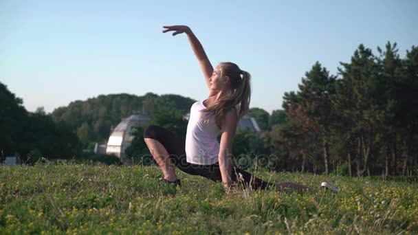Sportlerin mit blonden langen Haaren tun stretching Training im freien.