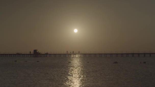 Siluety lidí, kteří jdou podél mola, večerní slunce v moři